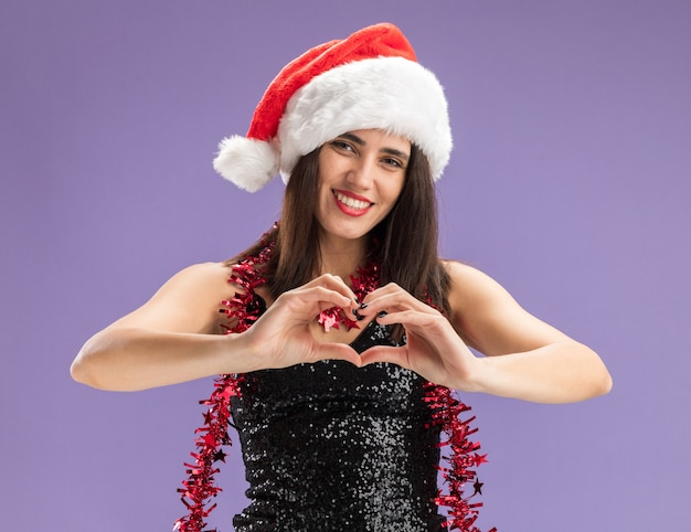 Smiling young beautiful girl wearing christmas hat with garland on neck showing heart gesture isolated on purple background