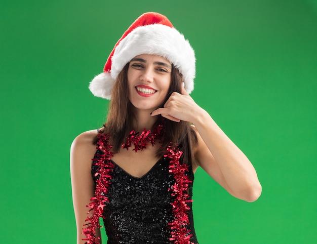 Sorridente giovane bella ragazza che indossa il cappello di natale con la ghirlanda sul collo che mostra il gesto di telefonata isolato su sfondo verde