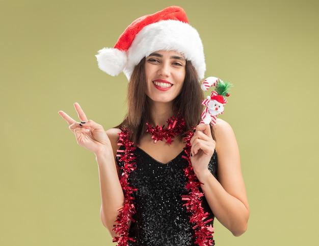 Улыбающаяся молодая красивая девушка в новогодней шапке с гирляндой на шее, держащая рождественскую игрушку, демонстрирует жест мира на оливково-зеленом фоне