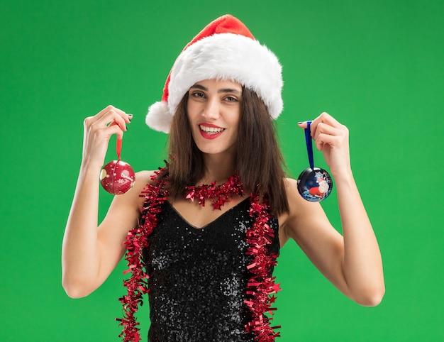 緑の壁に分離されたクリスマスツリーのボールを保持している首に花輪とクリスマス帽子をかぶって若い美しい少女