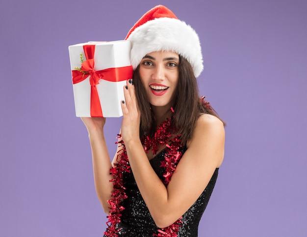보라색 배경에 고립 된 얼굴 주위에 선물 상자를 들고 목에 갈 랜드와 함께 크리스마스 모자를 쓰고 웃는 젊은 아름 다운 소녀