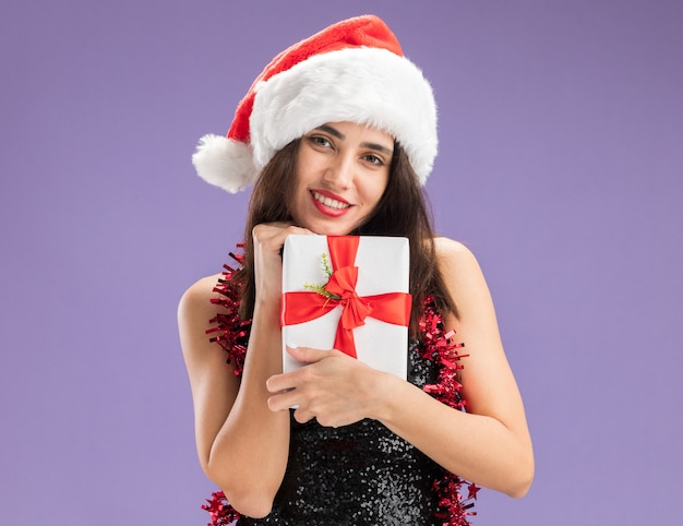 보라색 배경에 고립 된 선물 상자를 들고 목에 갈 랜드와 함께 크리스마스 모자를 쓰고 웃는 젊은 아름 다운 소녀