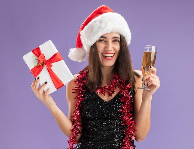보라색 배경에 고립 된 샴페인 잔 선물 상자를 들고 목에 갈 랜드와 함께 크리스마스 모자를 쓰고 웃는 젊은 아름 다운 소녀