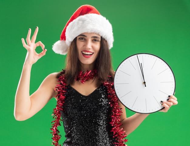 녹색 배경에 고립 괜찮아 제스처를 보여주는 벽 시계를 들고 목에 갈 랜드와 함께 크리스마스 모자를 쓰고 웃는 젊은 아름다운 소녀