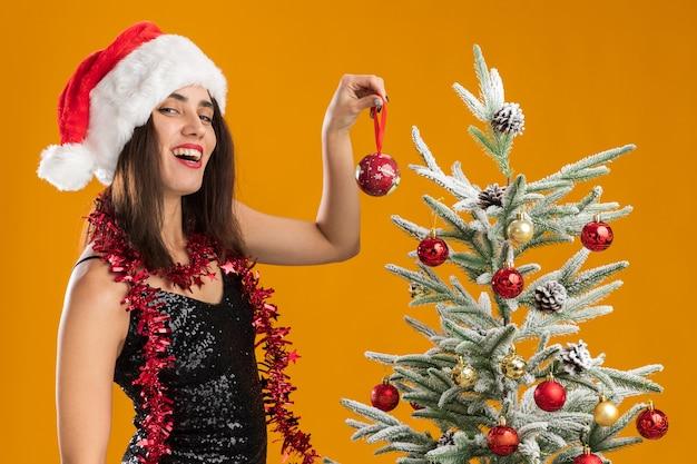 Улыбающаяся молодая красивая девушка в новогодней шапке с гирляндой на шее стоит рядом с елкой и держит елочный шар на оранжевом фоне