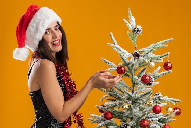 オレンジ色の壁に分離された舌を示すクリスマスツリーの近くに立っている首に花輪とクリスマス帽子をかぶって笑顔の若い美しい少女