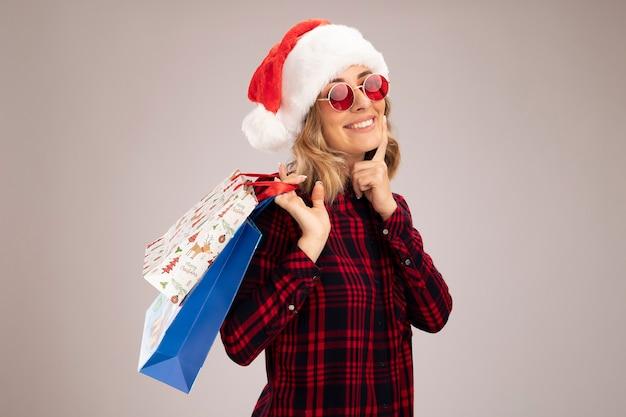 Sorridente giovane bella ragazza che indossa il cappello di natale con gli occhiali che tengono la borsa regalo sulla spalla mettendo il dito sulla guancia isolato su sfondo bianco