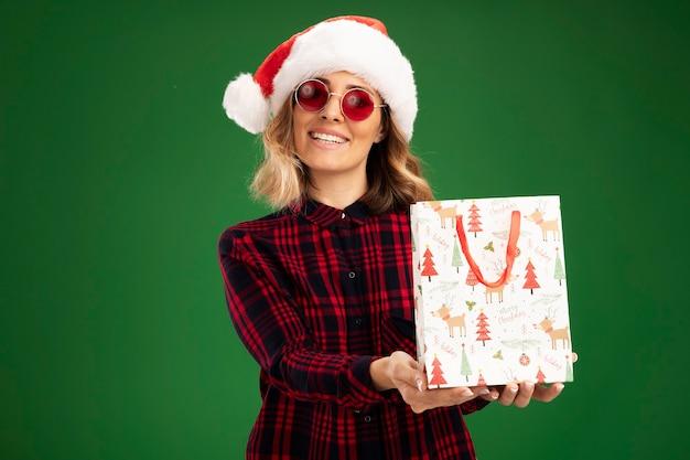 Sorridente giovane bella ragazza che indossa il cappello di natale con gli occhiali che tengono fuori la borsa regalo in telecamera isolata su sfondo verde