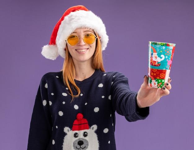 紫色の壁に分離されたクリスマス カップを保持している眼鏡をかけたクリスマス セーターと帽子を身に着けている笑顔の美しい少女