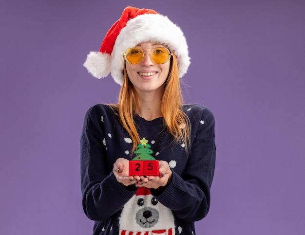 Smiling young beautiful girl wearing christmas sweater and hat with glasses holding christmas toy isolated on purple wall