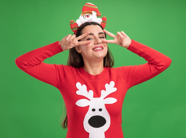Smiling young beautiful girl wearing christmas sweater with christmas hair hoop showing peace gesture isolated on green wall