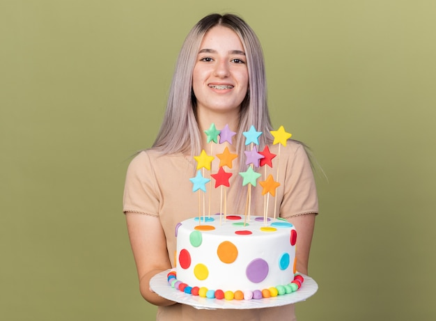 Smiling young beautiful girl wearing dental braces holding out cake at camera