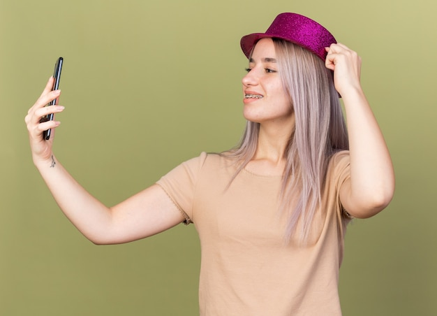 Smiling young beautiful girl wearing dental braces and party hat holding and looking at phone isolated on olive green wall