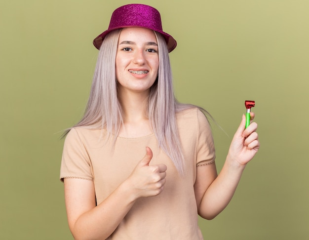 Smiling young beautiful girl wearing dental braces with party hat holding blowing whistle showing thumb up isolated on olive green wall