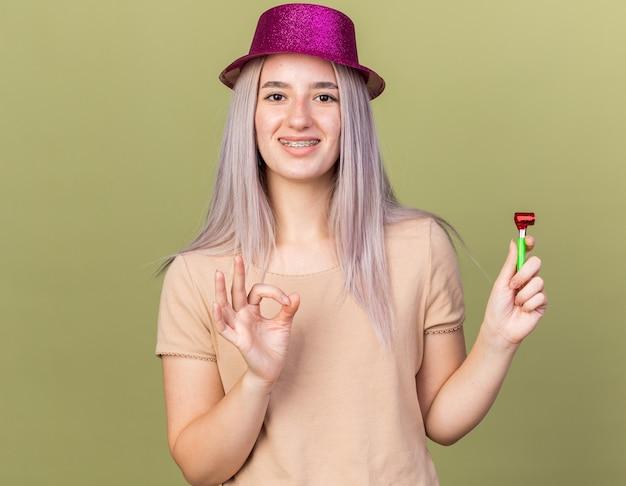 Sorridente giovane bella ragazza che indossa bretelle dentali con cappello da festa che tiene un fischio di festa che mostra un gesto ok