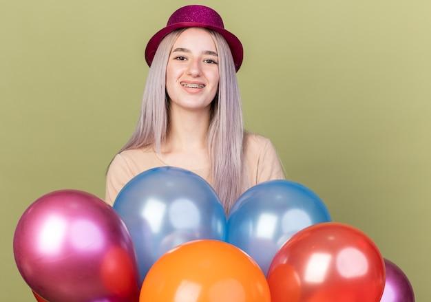 Sorridente giovane bella ragazza che indossa bretelle dentali con cappello da festa in piedi dietro palloncini