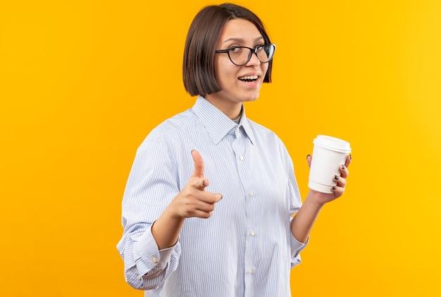 Sorridente giovane bella ragazza con gli occhiali tenendo la tazza di caffè punti in camera