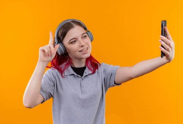 ヘッドフォンで灰色のtシャツを着て笑顔の若い美しい少女は、孤立した黄色の背景でselfieを取ることを指さします