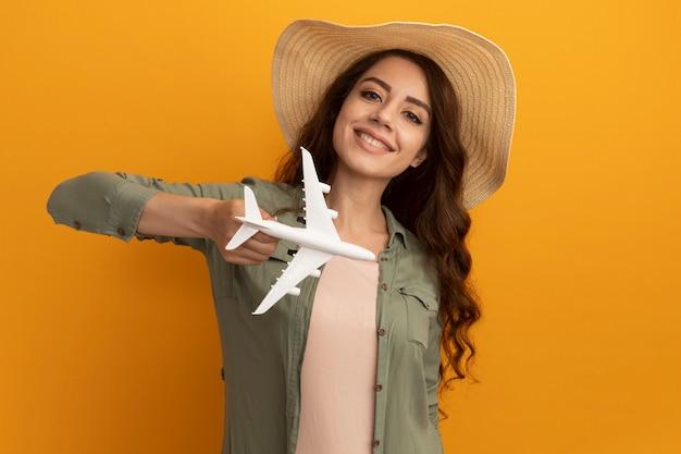 Улыбающаяся молодая красивая девушка в оливково-зеленой футболке и шляпе держит игрушечный самолетик на желтой стене
