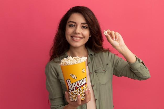 분홍색 벽에 고립 된 팝콘 평화와 팝콘 양동이 들고 올리브 녹색 티셔츠를 입고 젊은 아름 다운 소녀 미소