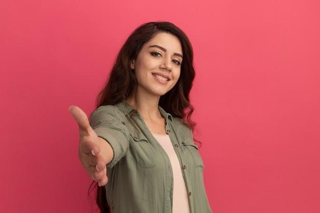 Sorridente giovane bella ragazza che indossa la maglietta verde oliva tendendo la mano alla macchina fotografica isolata sulla parete rosa con lo spazio della copia