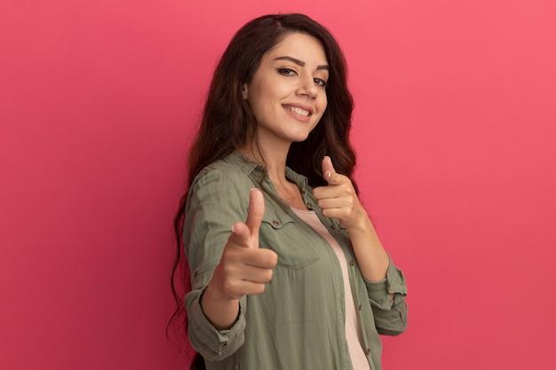 Улыбающаяся молодая красивая девушка в оливково-зеленой футболке указывает на камеру, изолированную на розовой стене