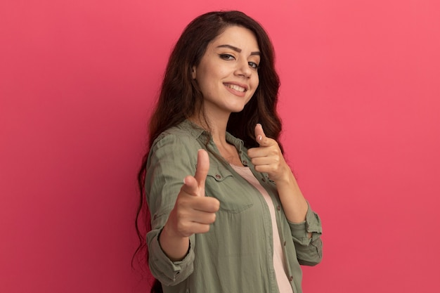 La giovane bella ragazza sorridente che indossa la maglietta verde oliva indica la macchina fotografica isolata sulla parete rosa