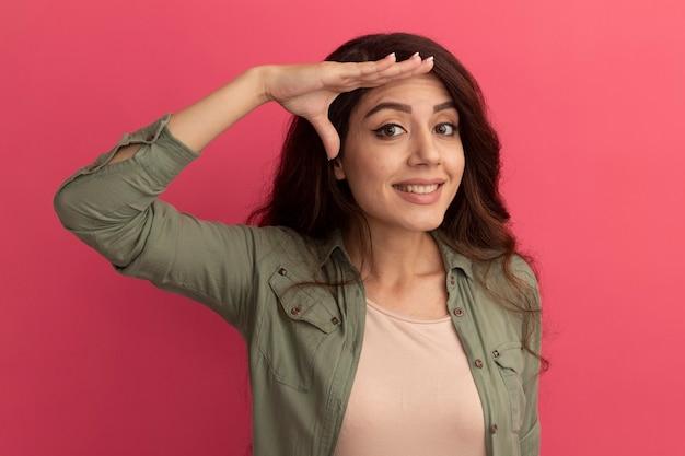 Улыбающаяся молодая красивая девушка в оливково-зеленой футболке, показывающая жест салюта, изолирована на розовой стене