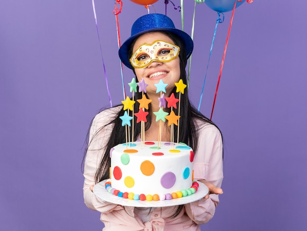 パーティーハットと仮面舞踏会のアイマスクを身に着けている若い美しい少女が前の風船に立って、青い壁で隔離のケーキを保持している笑顔