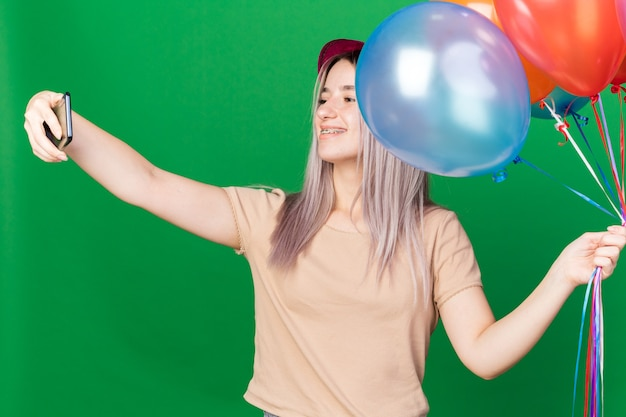 Smiling young beautiful girl wearing party hat and braces holding balloons take a selfie isolated on green wall