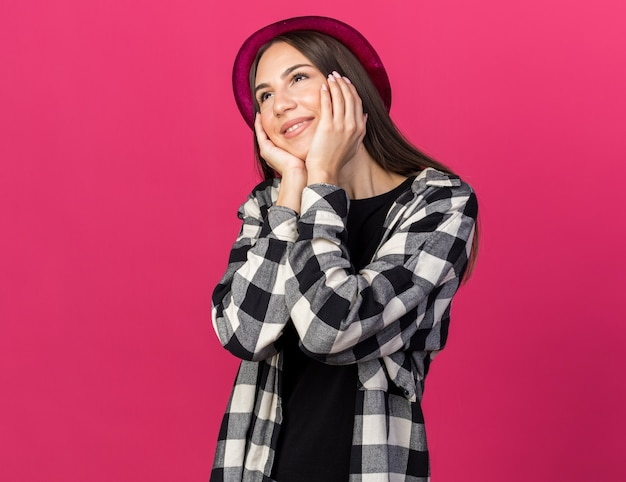 ピンクの壁で隔離の顔にパーティーハットで覆われた頬を身に着けている若い美しい少女の笑顔