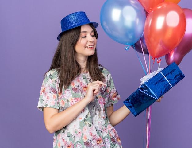 Улыбающаяся молодая красивая девушка в партийной шляпе держит и смотрит на воздушные шары с подарочной коробкой