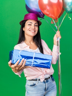 Smiling young beautiful girl wearing party hat holding balloons holding gift box