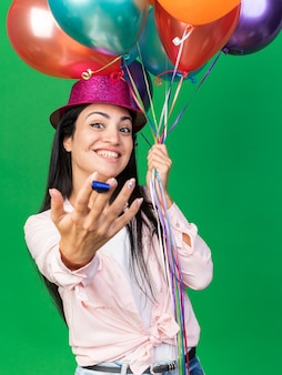 Smiling young beautiful girl wearing party hat holding balloons and holding out party whistle isolated on green wall