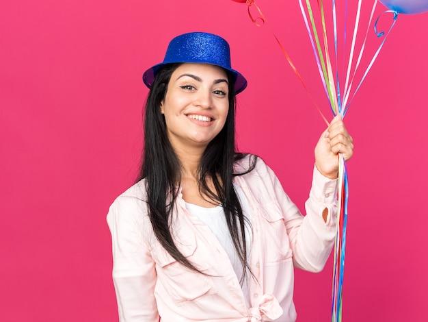 Sorridente giovane bella ragazza che indossa cappello da festa tenendo palloncini isolati su parete rosa