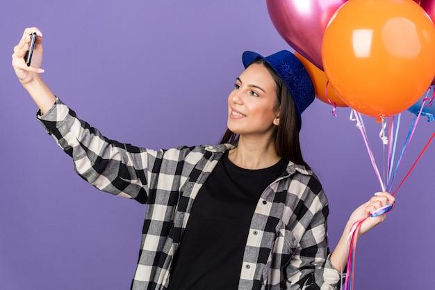 風船を持ってパーティーハットをかぶって笑顔の若い美しい女の子が自分撮りを取ります