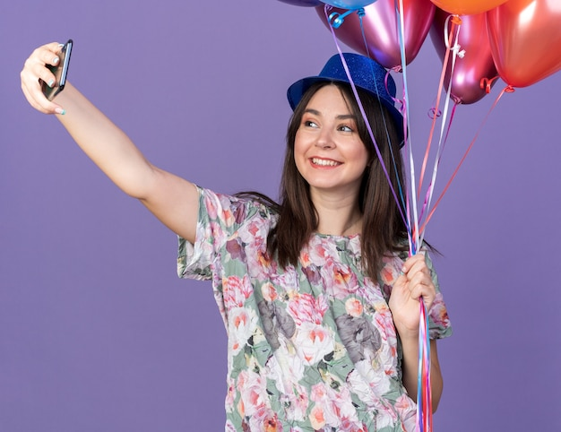 Smiling young beautiful girl wearing party hat holding balloons take a selfie isolated on blue wall