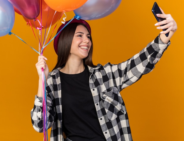 Smiling young beautiful girl wearing party hat holding balloons and take a selfie isolated on orange wall