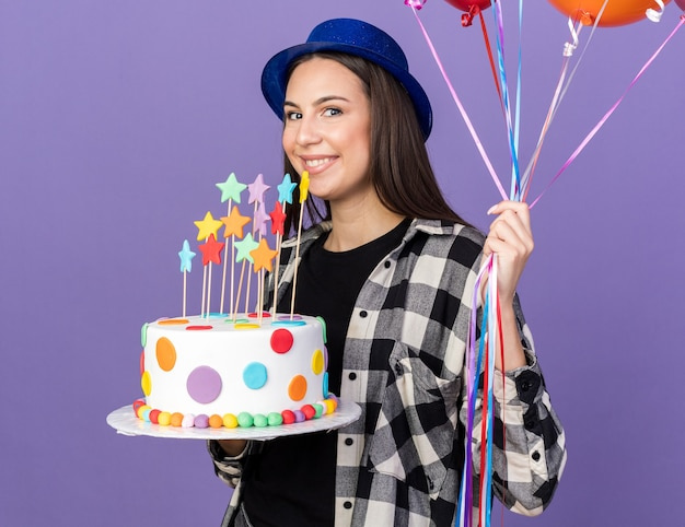 Smiling young beautiful girl wearing party hat holding balloons with cake isolated on blue wall