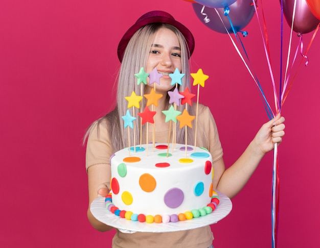 Smiling young beautiful girl wearing party hat holding balloons with cake isolated on pink wall