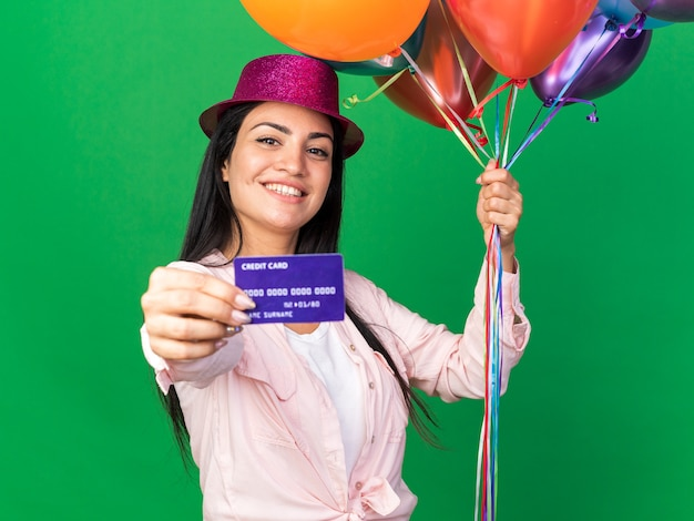 Smiling young beautiful girl wearing party hat holding balloons with credit card isolated on green wall