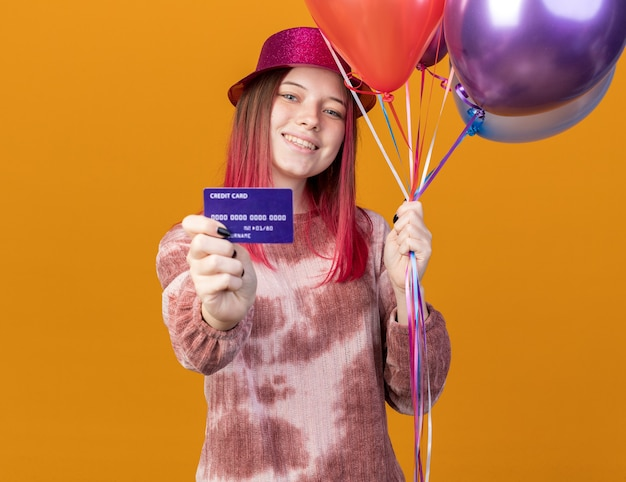 Smiling young beautiful girl wearing party hat holding balloons with credit card isolated on orange wall