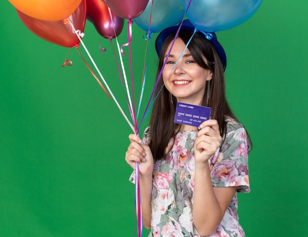 Smiling young beautiful girl wearing party hat holding balloons with credit card