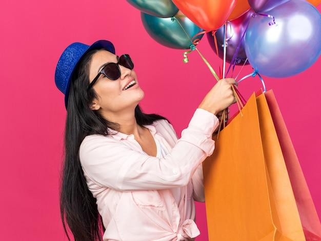 ピンクの壁に分離されたギフトバッグと風船を保持しているパーティーハットを身に着けている若い美しい少女の笑顔
