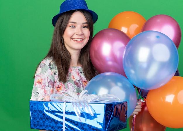Sorridente giovane bella ragazza che indossa cappello da festa che tiene palloncini con scatola regalo isolata sul muro verde