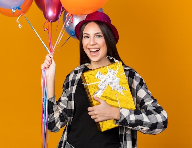 Улыбающаяся молодая красивая девушка в партийной шляпе держит воздушные шары с подарочной коробкой, изолированной на оранжевой стене