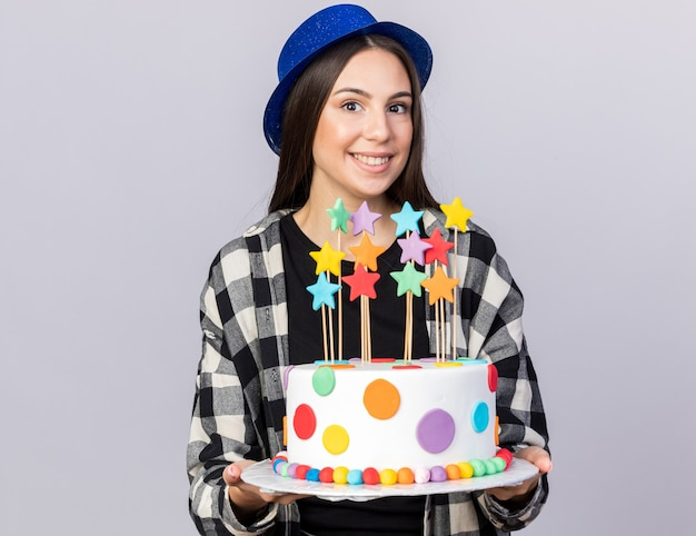 白い壁に分離されたケーキを保持しているパーティー帽子をかぶって笑顔の若い美しい少女