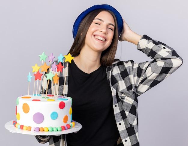 Sorridente giovane bella ragazza che indossa cappello da festa tenendo la torta mettendo la mano sulla testa isolata sul muro bianco