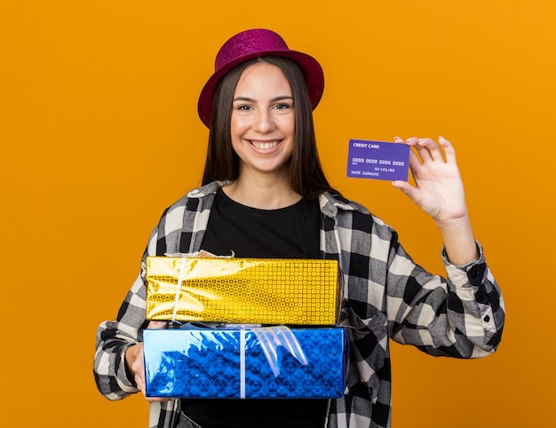 Smiling young beautiful girl wearing party hat holding gift boxes and credit card