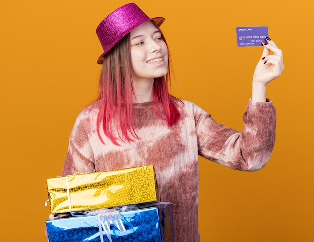 Smiling young beautiful girl wearing party hat holding gift boxes and looking at credit card in her hand